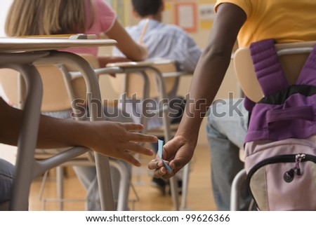 Students passing notes in class - stock photo