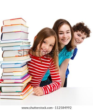 Students peeking behind pile of books on white background - stock photo
