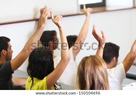 students put hand up in class room - stock photo