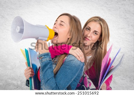 Students shouting by megaphone over textured background - stock photo