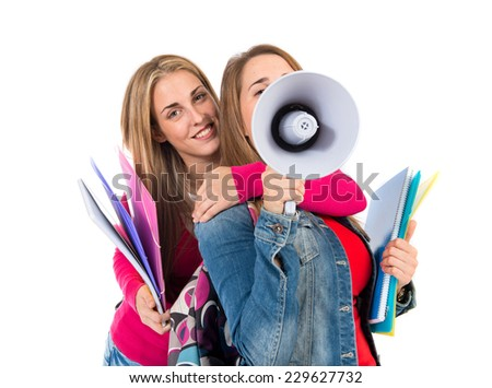 Students shouting by megaphone over white background - stock photo