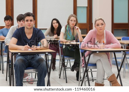 Students sitting at the classroom while listening - stock photo