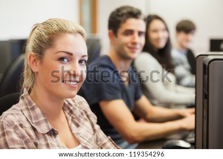 Students sitting at the computer room smiling - stock photo