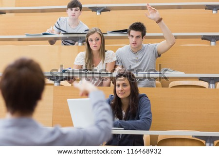 Students sitting at the lecture hall with man raising hand to ask question and lecturer is pointing at him - stock photo