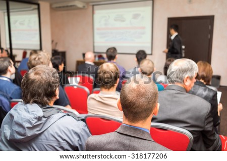 students sitting in a lecture room with teacher in front of the class with white projector slide screen - stock photo