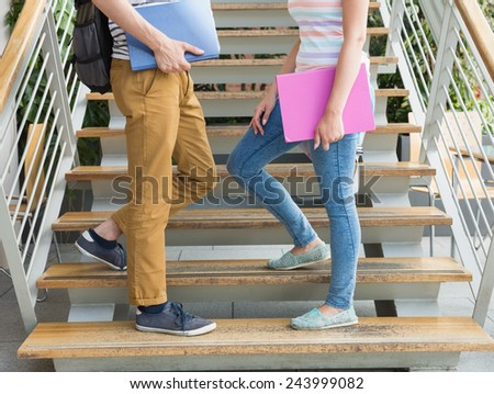 Students standing on steps together at the university - stock photo