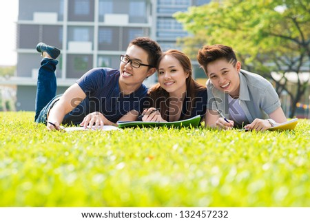 Students studying on the campus lawn - stock photo