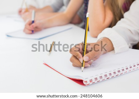 Students taking notes in class at the college - stock photo