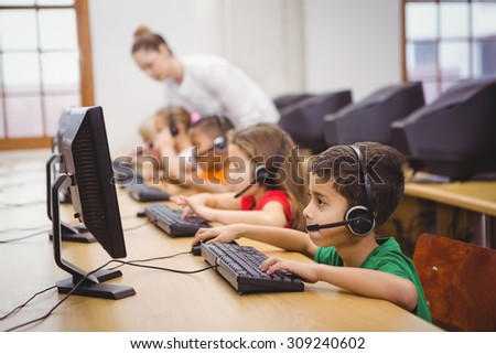 Students using computers in the classroom at the elementary school - stock photo