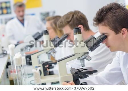 Students using microscopes - stock photo