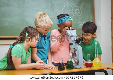 Students using science beakers and a microscope at the elementary school - stock photo