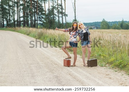 Students wearing sunglasses hitchhiking with cardboard on road - stock photo