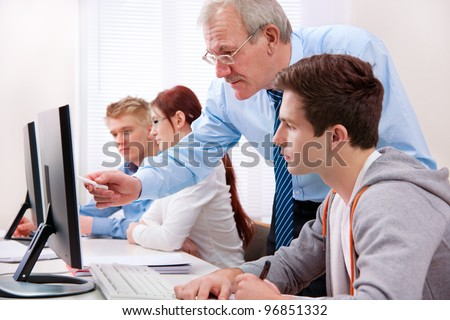 Students with a teacher in computer classroom - stock photo