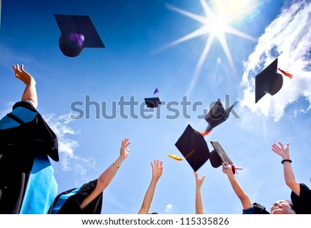 Students with congratulations throwing graduation hats in the air celebrating