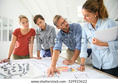 Students with teacher working on project around table - stock photo