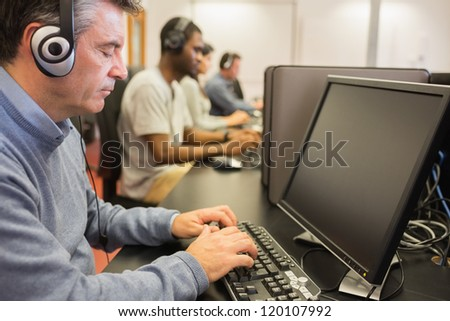 Students working with computers in classroom - stock photo