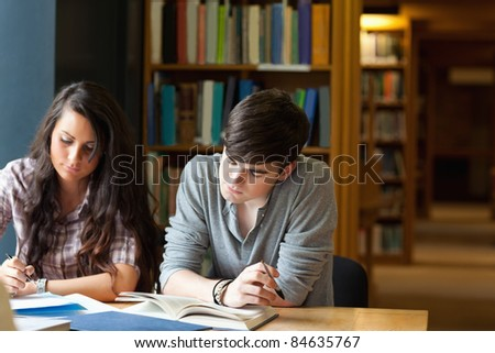 Students writing an essay in a library - stock photo