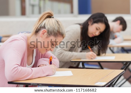 Students writing in the exam hall in college - stock photo