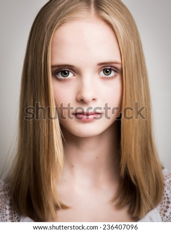 Studio art portrait of a beautiful young blond teenage girl with long hair and blue/grey hair dressed isolated against a white/grey background.