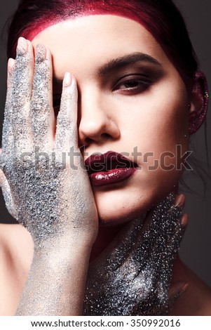 Studio beauty portrait of attractive woman with creative make-up and glitter and spangle on hands - stock photo