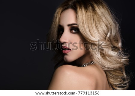 Studio beauty portrait of gorgeous blonde woman on black background