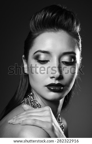 Studio beauty portrait of woman with gold necklace and make-up