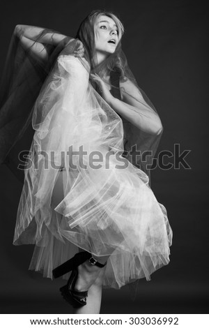 Studio, black and white photo of a girl ballerina, in a flying skirt, on black background - stock photo
