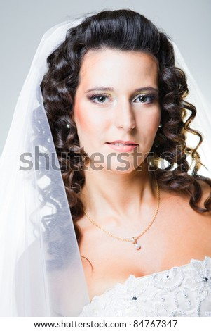 Studio close-up portrait of attractive bride with white veil