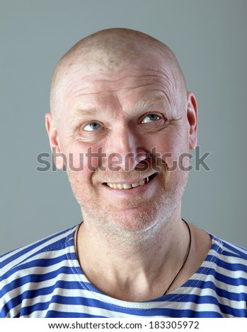 studio close-up portrait of the adult bald white man in a striped vest with a blissful view looking up
