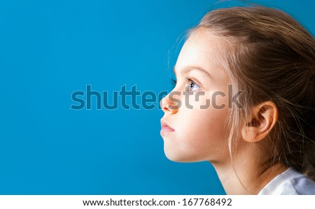 Studio closeup portrait of little girl with serious face in profile - stock photo