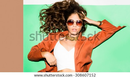 Studio closeup trendy portrait of young sexy funny fashion girl posing colorful wall background in summer style outfit,stylish jacket,and white t-short.cool,trendy sunglasses,curly hairstyle,laying - stock photo