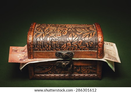Studio conceptual image, wooden decorated vintage suitcase full of euro banknotes.  - stock photo