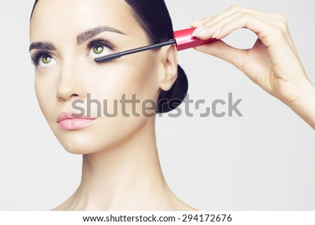 Studio fashion photo of beautiful young lady applied mascara.  Beauty and care. Extension eyelashes. Spa salon. Perfect face makeup - stock photo