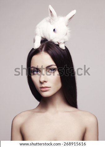 Studio fashion portrait of beautiful lady with white rabbit - stock photo
