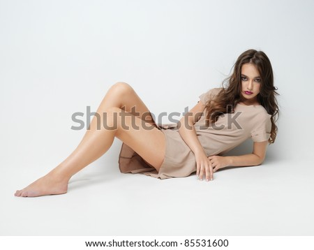 studio fashion portrait of beautiful young woman, sitting, on white background, posing at camera