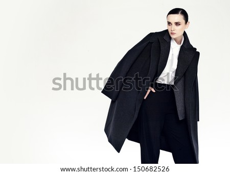 studio fashion portrait of yong pretty woman in black coat - stock photo