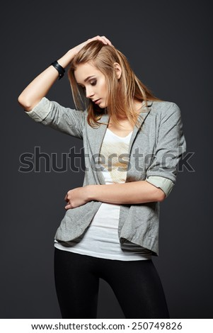 Studio fashion shot: a beautiful young girl in leggings, jacket and shirt - stock photo