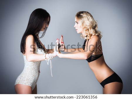 Studio fashion shot: the challenge between two lovely women (blonde and brunette) in underwear  - stock photo