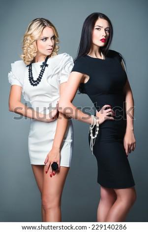 Studio fashion shot: two beautiful women (blonde and brunette) wearing dresses - stock photo