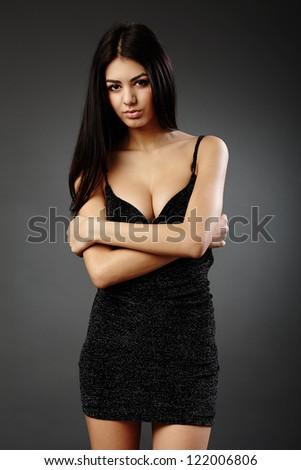 Studio glamour shot of a beautiful hispanic woman in black dress - stock photo