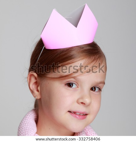 Studio image of a beautiful cheerful little girl in a pink knitted dress with a crown on his head on a gray background on Holiday - stock photo