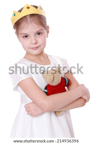 Studio image of a beautiful little girl in a white dress with a crown holding a teddy bear isolated on white