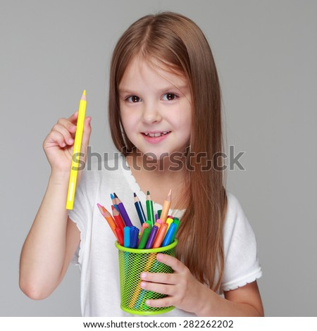 Studio image of a beautiful young caucasian girl in a white dress with colored pencils on a gray background - stock photo