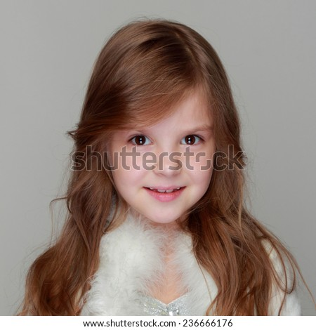 Studio image of a charming young girl in a shiny dress with fur cape holding a Christmas decoration on Holiday - stock photo