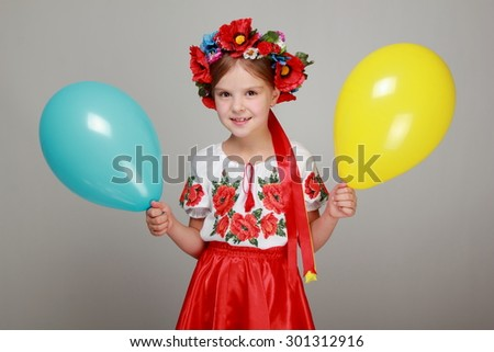 Studio image of a happy cute little girl in the Ukrainian national costume holding a yellow and blue air balloon on a gray background on Holiday - stock photo