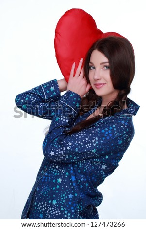 Studio image of sleeping woman with heart-shaped pillow on white background on Holiday theme - stock photo