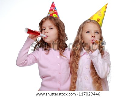 Studio image of two friends with toy horns isolated on white background on Holiday theme/Joyful kids