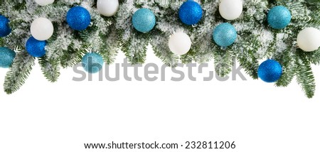 Studio isolated lush fir branches with snow and baubles in blue and white, as a bow-shaped border on pure white background - stock photo