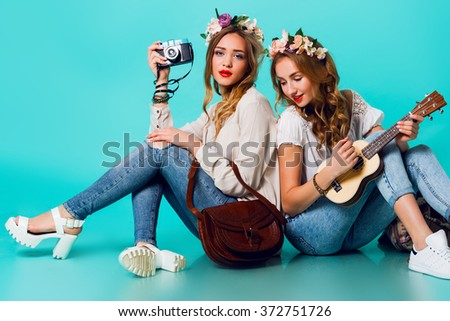 Studio lifestyle portrait of  two pretty young blonde   happy girls having fun. Making pictures in hipster style  on retro camera, wearing stylish vintage boho outfits and  flowers wreath. Spring. - stock photo