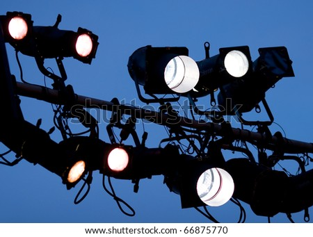 Studio lighting equipment high above an outdoor theatrical performance.
